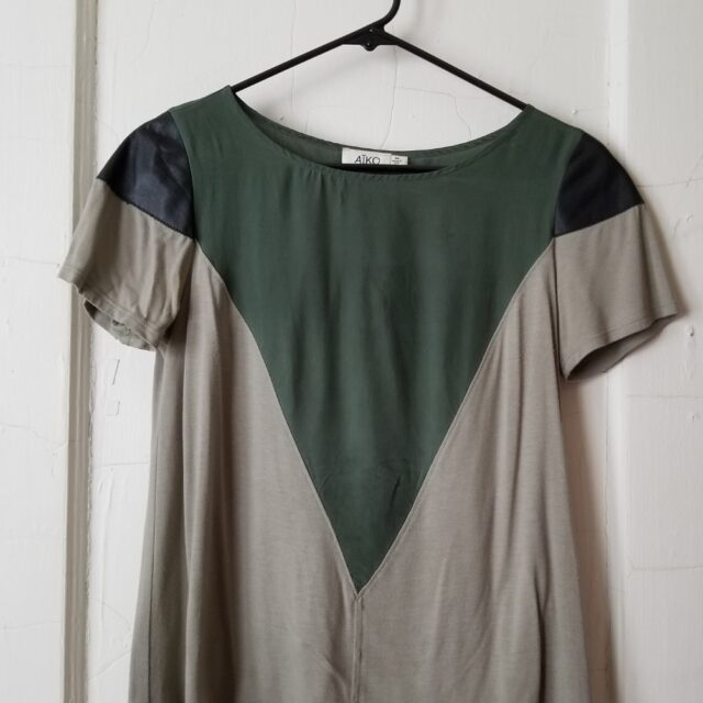 Sage green and tan shirt with black leather trim, hanging on a white door.