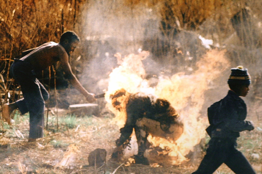 A man hacking at a man set on fire in South Africa.